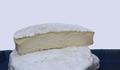 ein halbiertes Stück Ziegenweichkäse liegt auf einem Ganzen