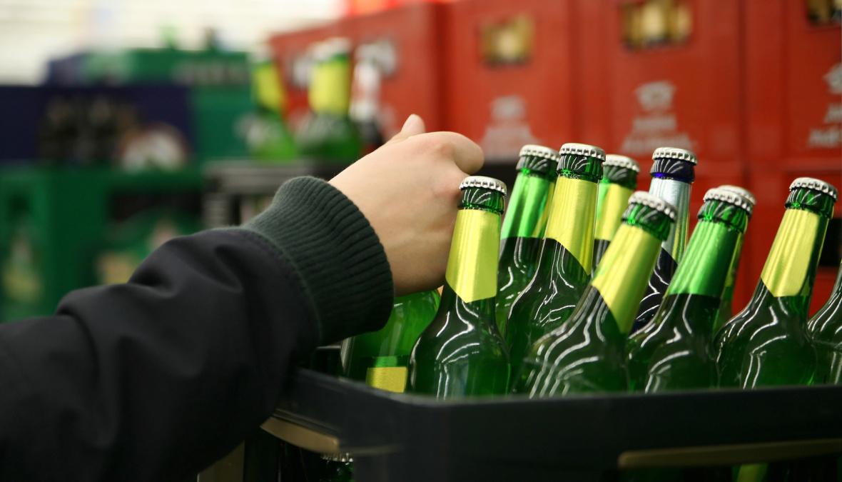 eine Hand nimmt sich eine Bierflasche von mehreren weg