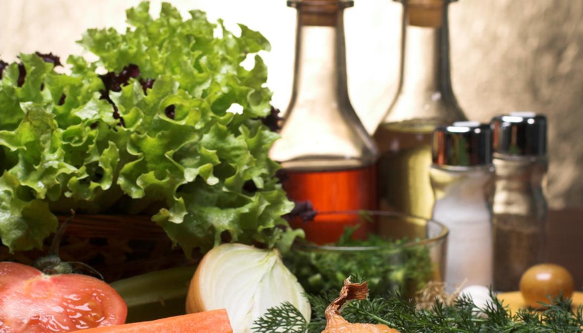 Salat mit Essig und Ölflasche im Hintergrund