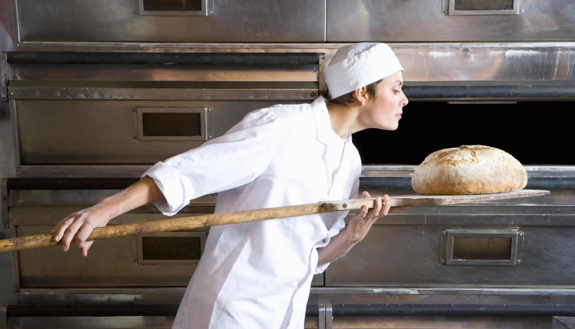 eine Bäckerin holt ein gebackenes Brot aus dem Ofen
